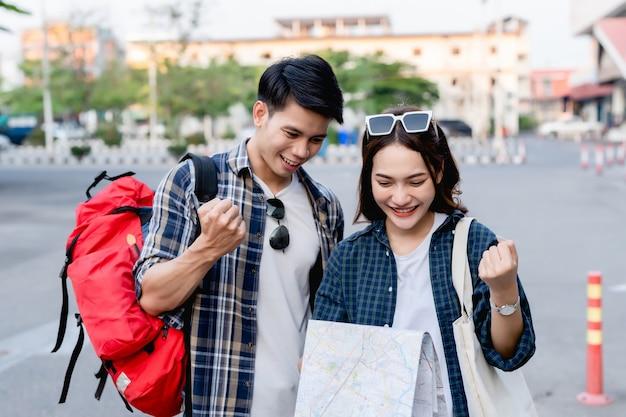 Szczęśliwa para azjatyckich turystów podróżujących z plecakami, trzymając papierową mapę i szukając kierunku podczas podróży, uśmiechają się z zadowoleniem, gdy dotarli na miejsce na papierowej mapie docelowej.