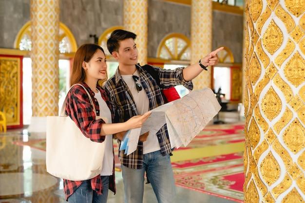 Szczęśliwa para azjatyckich turystów z plecakami trzymających papierową mapę i szukających kierunku podczas podróży w tajskiej świątyni na wakacjach w tajlandii, przystojny mężczyzna wskazujący i sprawdzający mapę