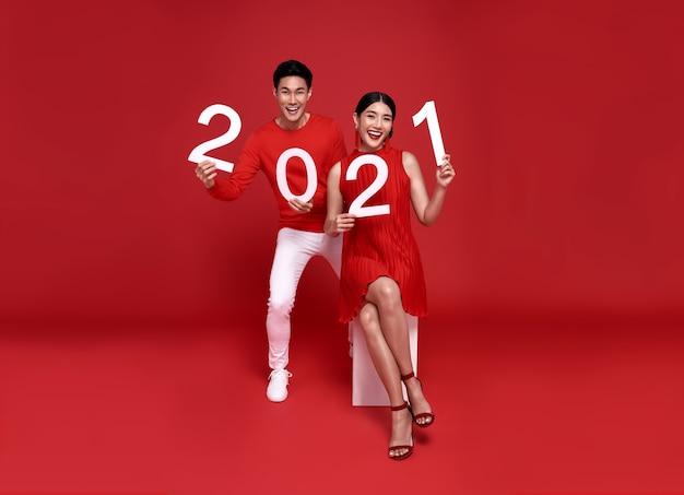 Szczęśliwa para azjatyckich w czerwonym stroju casual pokazująca numer 2021 powitanie szczęśliwego nowego roku z uśmiechem na jasnoczerwonym.