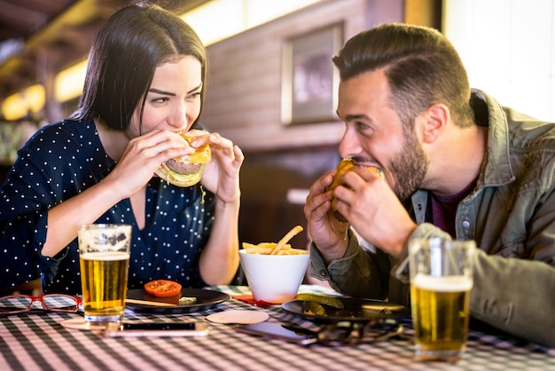 Szczęśliwa para bawi się jedząc burgera w restauracji pub fast food