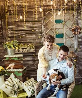 Szczęśliwa para bawi się z ukochanym psem w salonie