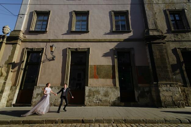 Szczęśliwa para biega wpólnie w ulicie w zimie