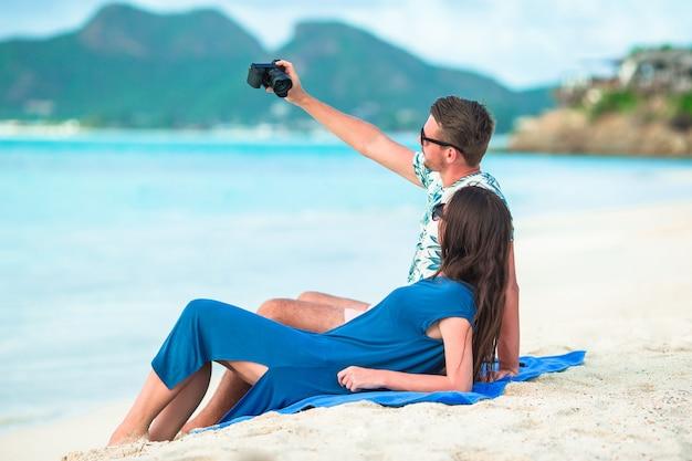 Szczęśliwa para bierze selfie fotografię na biel plaży. dwie osoby dorosłe spędzające wakacje na egzotycznej tropikalnej plaży