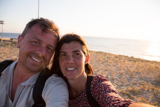 Szczęśliwa para bierze selfie fotografię z mądrze telefonem przy zmierzchem na plaży