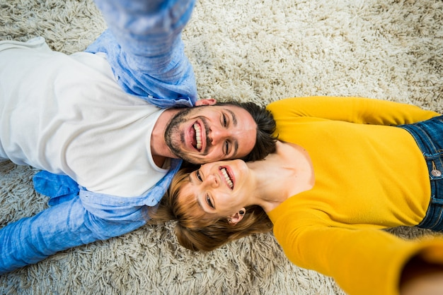 Szczęśliwa para bierze selfie lying on the beach na dywanie w domu. pojęcie o związku i ludziach