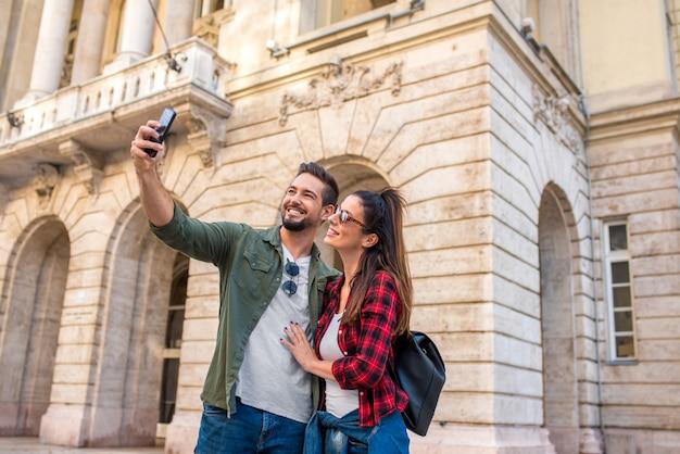 Szczęśliwa para bierze selfie podczas zwiedzania europejskiego miasta