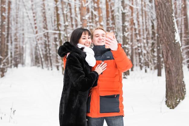 Szczęśliwa para biorąc obraz z smartphone na tle zimowego.