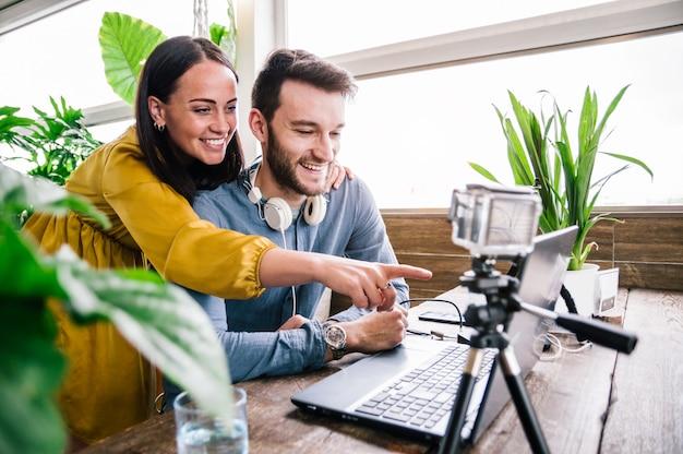 Szczęśliwa para blogerów nagrywających film przygotowujący się do opublikowania w sieciach społecznościowych