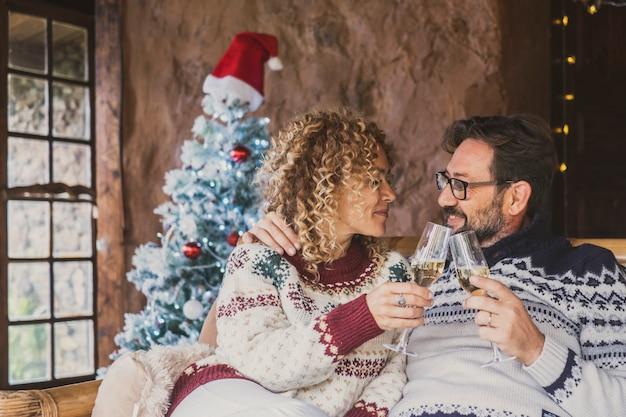 Szczęśliwa para brzęk wina podczas świąt bożego narodzenia w domu