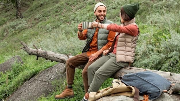 Szczęśliwa para ciesząc się gorącym napojem, siedząc na dzienniku