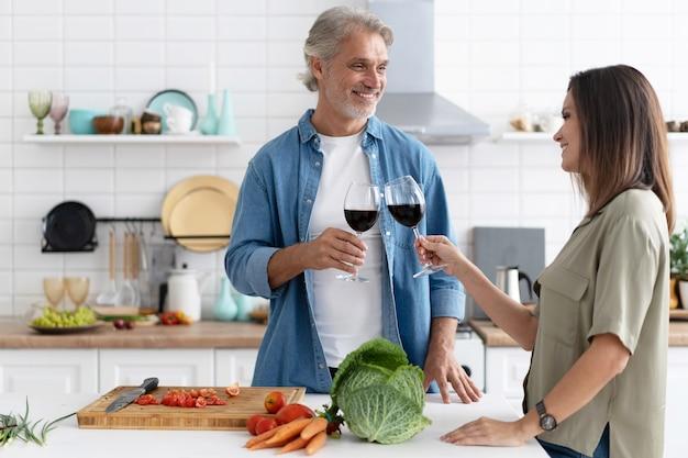 Szczęśliwa para ciesząc się winem podczas pracy w kuchni.