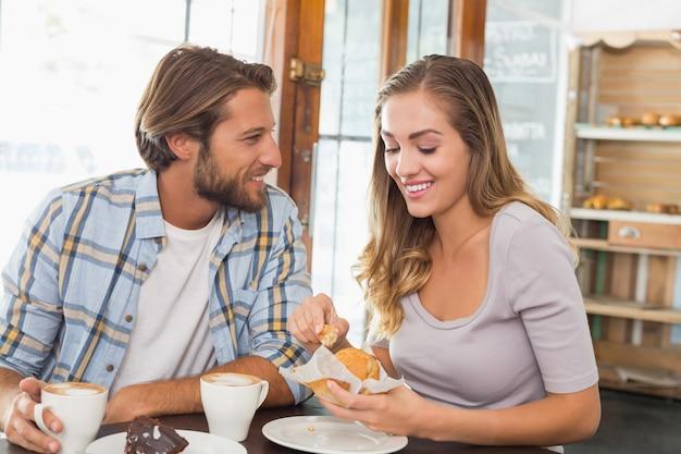 Szczęśliwa para cieszy się kawę i tort