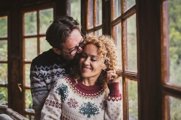 Szczęśliwa para cieszy się zimą w domu w świątecznych swetrach