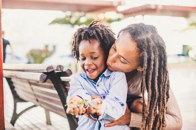 Szczęśliwa para czarna skóra afrykańska, matka i syn, młodzi razem bawią się i cieszą rekreacją na świeżym powietrzu w mieście