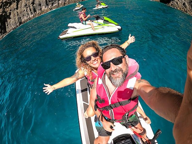 Szczęśliwa para dorosłych bawić się na escursion aktywności jet sky w letnie wakacje nad morzem