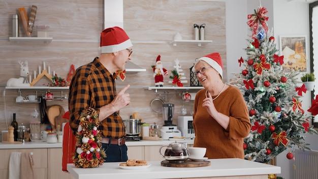 Szczęśliwa para dziadków rodziny dzieląca się prezentem ze wstążką na nim