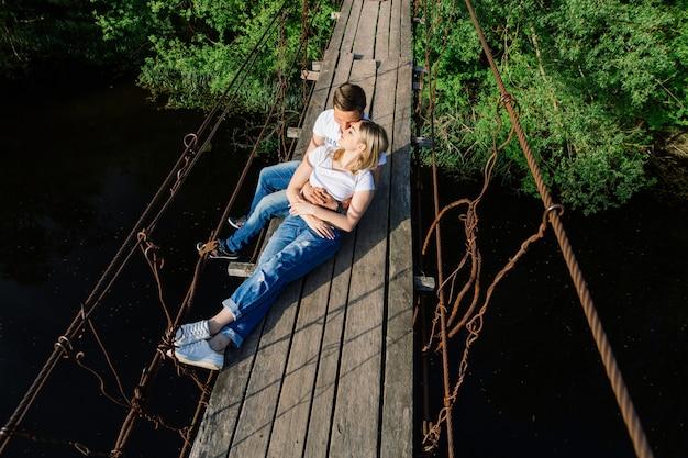 Szczęśliwa para emocjonalne przytulanie na drewniany most. historia miłości. mężczyzna i kobieta zakochana spacery na świeżym powietrzu w lecie. szczęśliwa uśmiechnięta marzy para razem na zewnątrz. aktywność romantyczna data. romantyczny moment