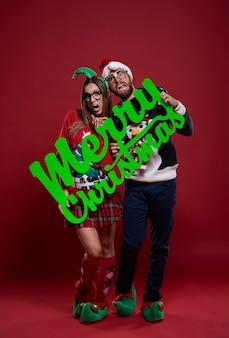 Szczęśliwa para frajerów w ubrania świąteczne na białym tle