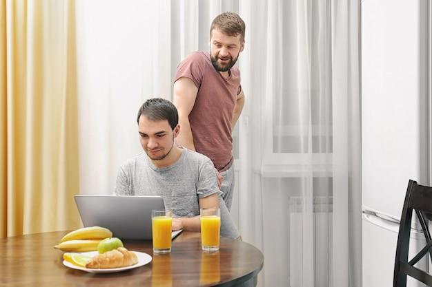 Szczęśliwa para gejów je śniadanie w kuchni i korzysta z laptopa