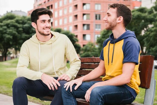 Szczęśliwa para gejów siedzi na drewnianej ławce w parku