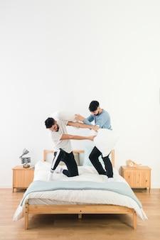 Szczęśliwa para gejów walki z białą poduszką na łóżku