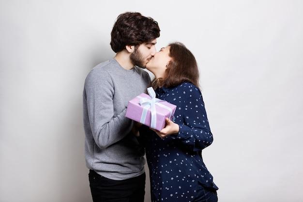 Szczęśliwa para gospodarstwa różowe pudełko całuje się namiętnie