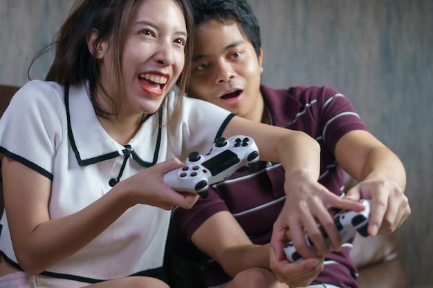 Szczęśliwa para grając w gry konsolowe, kobieta oszukuje w grach wideo.