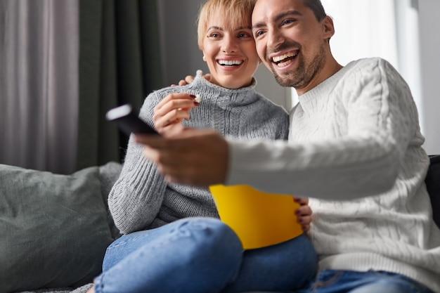 Szczęśliwa para jedzenie popcornu i oglądanie telewizji