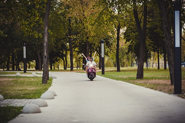 Szczęśliwa para jedzie na skuterze