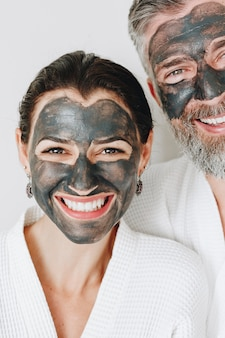 Szczęśliwa para jest ubranym węgiel drzewny maskę