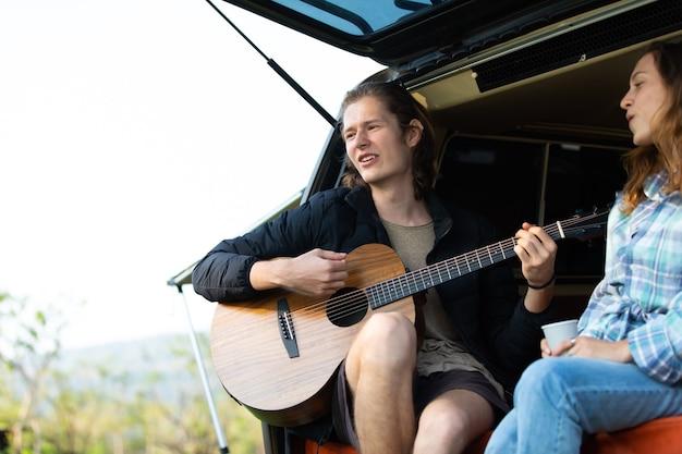 Szczęśliwa para kaukaska gra na gitarze na tle samochodu namiotowego