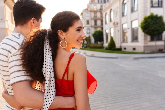 Szczęśliwa para kaukaska uśmiechnięta i przytulająca się podczas spaceru ulicą miasta w pobliżu pięknych budynków