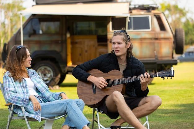 Szczęśliwa para kaukaski gra na gitarze na tle samochodu namiotowego. młodzi ludzie spędzają razem czas na wycieczce na kemping.