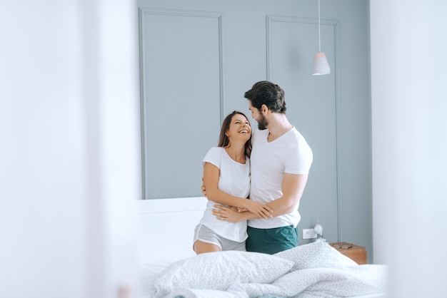 Szczęśliwa para kaukaski w piżamie, uśmiechając się i przytulając w łóżku rano. wnętrze sypialni.