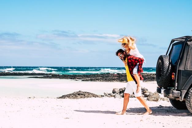 Szczęśliwa para kaukaskich ludzi bawi się razem na tropikalnej plaży z białym piaskiem z niebieskim eoceanem i niebem
