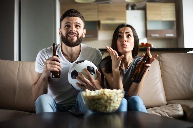 Szczęśliwa para kibiców ogląda mecz piłki nożnej w telewizji z przekąskami, piwem i piłką na kanapie
