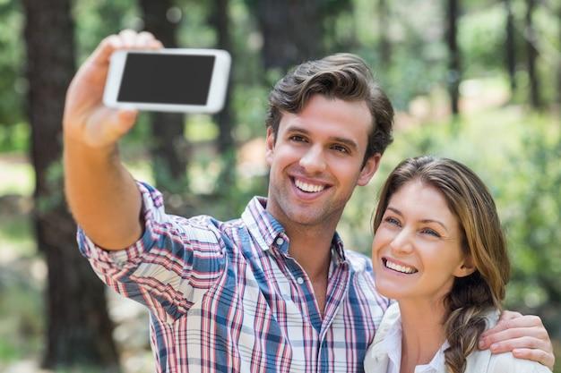 Szczęśliwa para klika selfie z mądrze telefonem