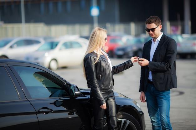 Szczęśliwa para kupić nowy nowoczesny czarny samochód