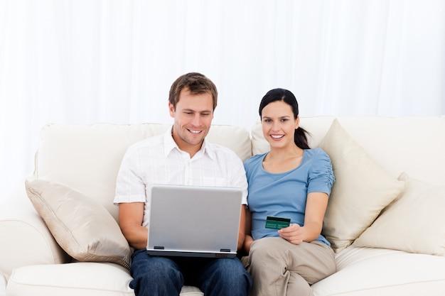 Szczęśliwa para kupuje online z laptopem i kredytową kartą na kanapie