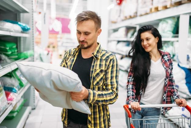 Szczęśliwa para kupuje poduszkę w supermarkecie. klienci płci męskiej i żeńskiej na rodzinne zakupy. mężczyzna i kobieta kupują towary do domu
