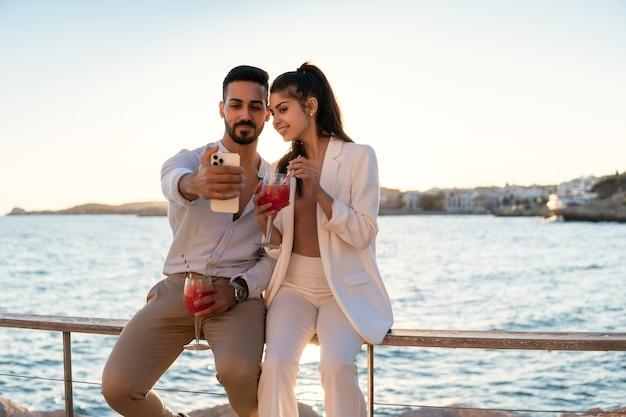 Szczęśliwa para latynoska biorąca selfie na promenadzie