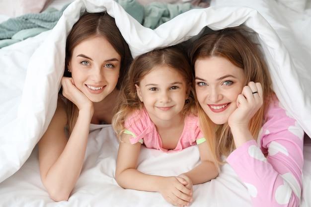 Szczęśliwa para lesbijek z córeczką leżącą pod kocem w łóżku