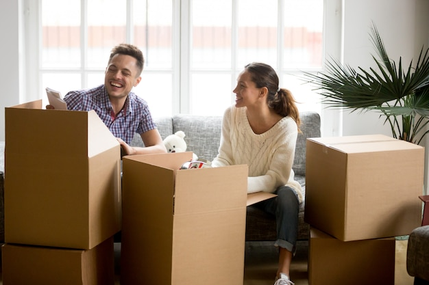Szczęśliwa para ma zabawę śmia się odpakowywać pudełka na poruszającym dniu