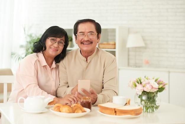 Szczęśliwa para małżeńska siedzi przy śniadaniowym stołem patrzeje kamerę