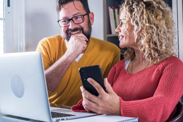 Szczęśliwa para mężczyzna i kobieta pracują w domu w inteligentnej pracy biurowej wraz z radością - cyfrowi współcześni dorośli ludzie w internetowej aktywności pracy w internecie - wesoła kobieta i mężczyzna przy użyciu komputera