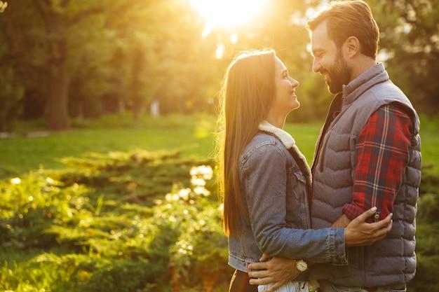 Szczęśliwa para mężczyzna i kobieta ubrani w codzienny strój przytulający się i patrzący na siebie podczas wspólnego spaceru po zielonym parku