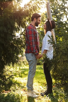 Szczęśliwa para mężczyzna i kobieta ubrani w codzienny strój, śmiejąc się, patrząc na siebie w zielonym parku