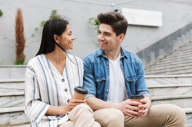 Szczęśliwa para mężczyzna i kobieta w zwykłych ubraniach pijąca kawę na wynos siedząc na ławce w pobliżu schodów na zewnątrz