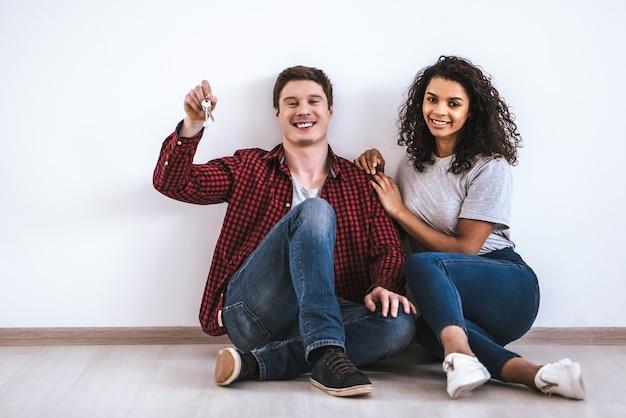 Szczęśliwa para międzynarodowa z kluczami siedząca na podłodze