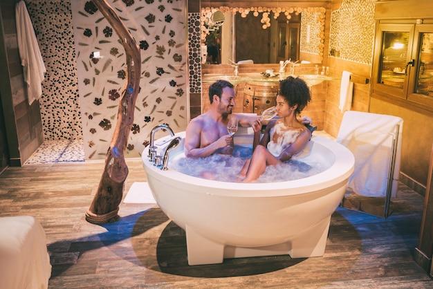 Szczęśliwa para międzyrasowa zrelaksowała się w jacuzzi, ciesząc się sobą i popijając wino